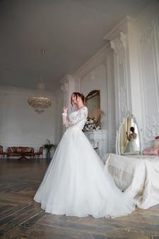 Portret van de bruid in een lichte studio, het meisje kijkt bedachtzaam opzij, met make-up en styling