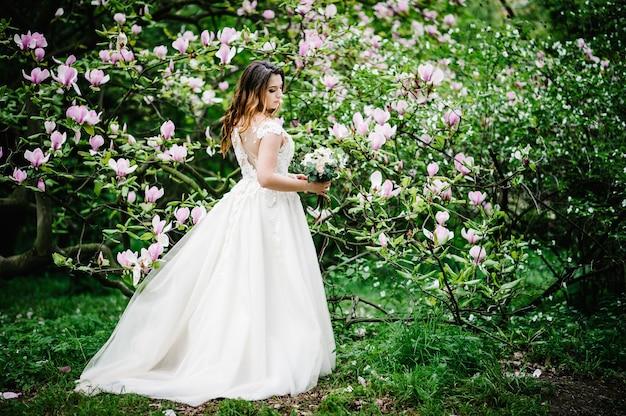Portret van de bruid met een bruiloft boeket staan terug, op de achtergrond aard van paarse, roze bloemen van magnolia en greens. buitenshuis. naar beneden kijken. volledige lengte.