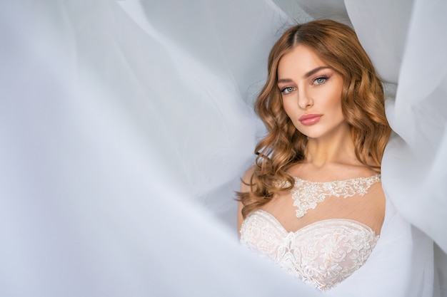 Portret van de bruid, mooie make-up, witte stoffen sluier