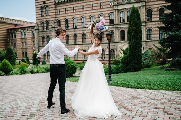 Portret van de bruidegom en de bruid lopen terug in de buurt van oud gebouw, oud huis buiten, buiten. pasgetrouwden lopen door de straten van de stad lviv. bruiloft wandelingen.