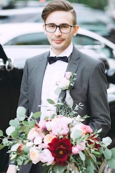 Portret van de bruidegom met een boeket bloemen voor de bruid in een pak close-up op de trouwdag.