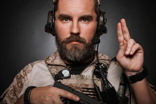Portret van de brutale man in militair uniform.