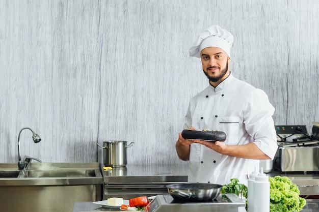 Portret van de chef-kok in de keuken van het restaurant met een kant en klare eieren