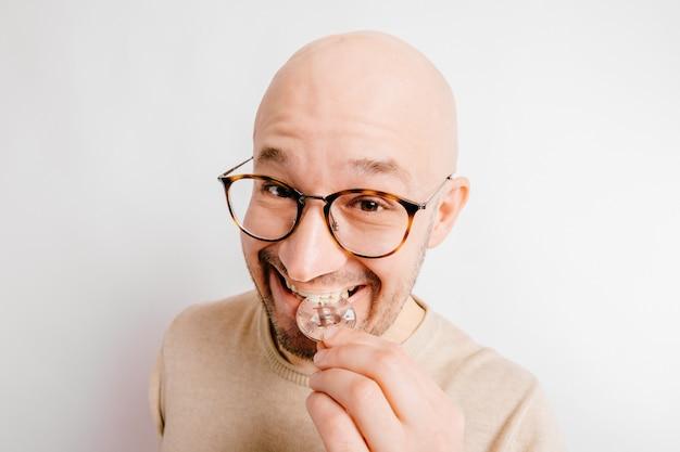 Portret van de close-up het grappige kale mens. gulzige cryptocurrency-mijnwerker die bitcoin-metalen munten bijt om de authenticiteit te controleren. succesvolle zakenman geld obsessie
