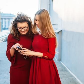 Portret van de de zomerstraat van de close-up het grappige modieuze manier van twee gelukkige meisjesvrienden openlucht stellen en het hebben van pret