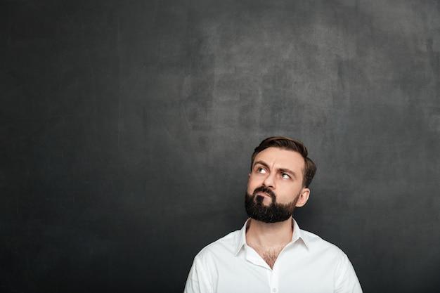 Portret van de donkerbruine ernstige mens in wit overhemd die omhoog met verdraaid gezicht kijken die of over donkergrijs denken herinneren