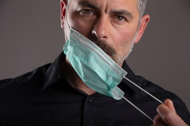 Portret van de ernstige houdingsmens die medisch beschermingsmasker over grijze studioachtergrond opstijgen. concept van persoonlijke verantwoordelijkheid tijdens quarantaine. overwinning op ziekte