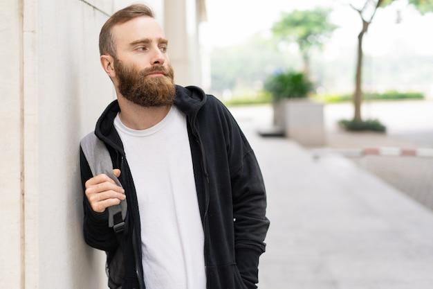 Portret van de ernstige jonge, bebaarde man met rugzak buitenshuis