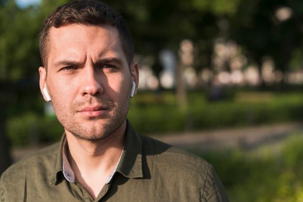 Portret van de ernstige mens die draadloze oortelefoon draagt die camera bekijkt
