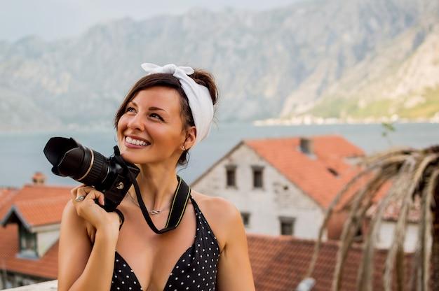 Portret van de fotografie van de vrouwenreiziger buiten met bergen wordt omringd die.