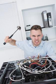 Portret van de gefrustreerde mens die cpu met hamer raakt