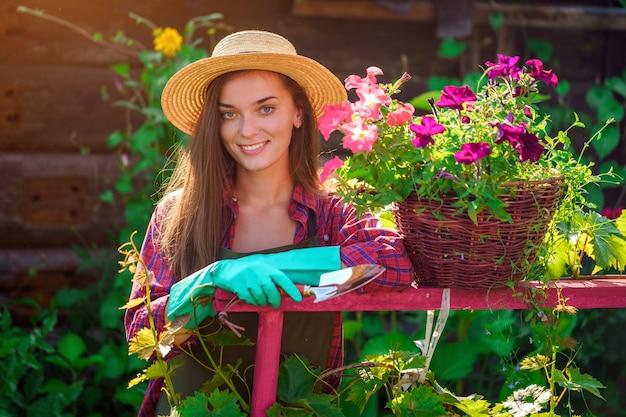 Portret van de gelukkige blije vrouw van de bloemisttuinman in hoed met bloempot van petunia en met schop in huistuin. tuinieren en sierteelt
