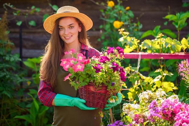 Portret van de gelukkige blije vrouw van de bloemisttuinman in hoed met bloempot van petunia in openlucht. tuinieren en sierteelt. groeiende bloem in huistuin