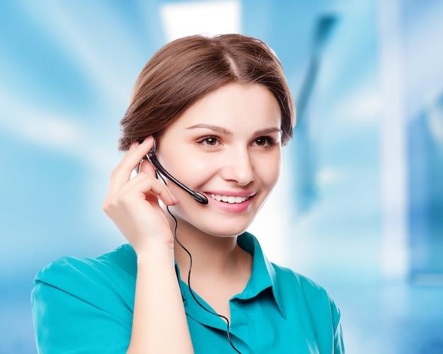 Portret van de gelukkige glimlachende vrolijke jonge exploitant van de steuntelefoon in hoofdtelefoon die copyspacegebied of iets tonen