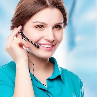 Portret van de gelukkige glimlachende vrolijke jonge exploitant van de steuntelefoon in hoofdtelefoon