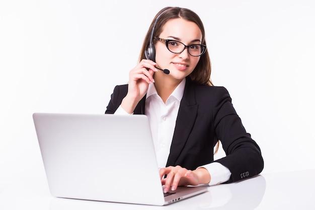 Portret van de gelukkige glimlachende vrolijke mooie jonge exploitant van de steuntelefoon in hoofdtelefoon met laptop, die over witte muur wordt geïsoleerd