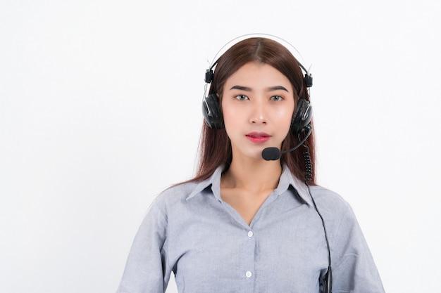 Portret van de gelukkige glimlachende vrouwelijke exploitant van de klantenondersteuningstelefoon die een wit overhemd met hoofdtelefoon draagt die de oortelefoon houdt die op wit wordt geïsoleerd