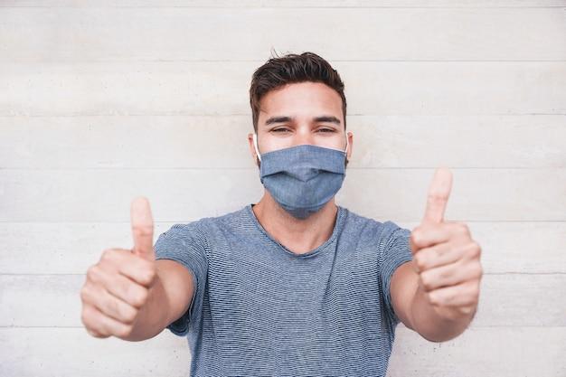 Portret van de gelukkige jonge mens die met omhoog duimen glimlachen terwijl het dragen van medisch beschermend masker voor coronavirus uitgespreide preventie