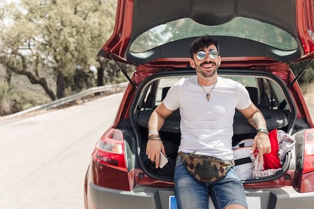 Portret van de gelukkige jonge mens die zich dichtbij de auto op weg bevindt