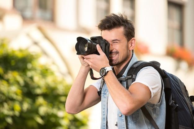 Portret van de gelukkige jonge mens, toeristen met camera in stad.