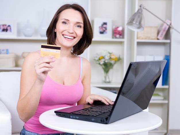 Portret van de gelukkige jonge mooie creditcard van de vrouwenholding en met behulp van laptop