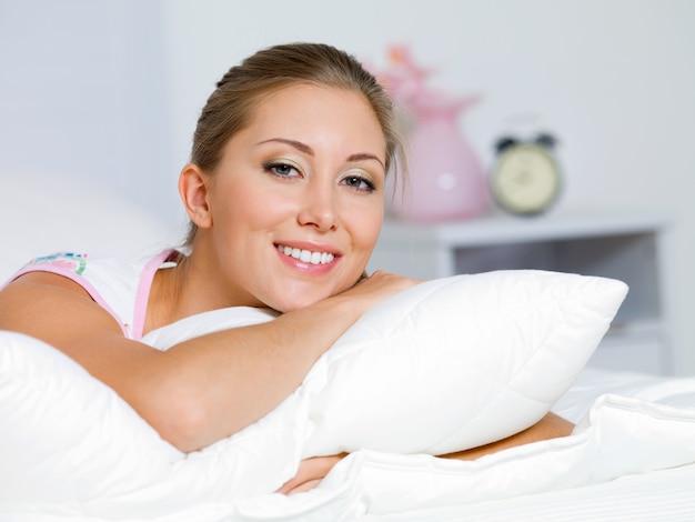 Portret van de gelukkige jonge vrouw die thuis op een bed rust