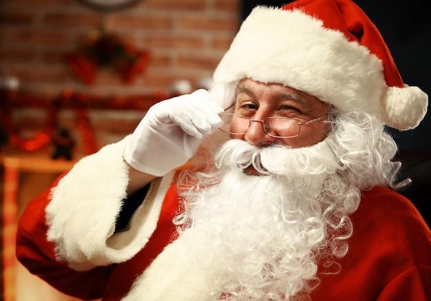 Portret van de gelukkige kerstman die kerstmisbrief in zijn handen houdt en camera bekijkt
