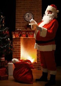 Portret van de gelukkige kerstman die zich in zijn kamer thuis dichtbij de kerstboom en grote zak bevindt en de kerstbrief of het verlanglijstje leest