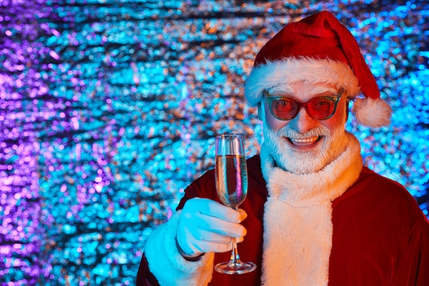Portret van de gelukkige kerstman in zonnebril die kerstmis met glas champagne vieren en glimlachen
