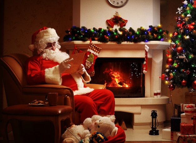 Portret van de gelukkige kerstman zit op zijn kamer thuis in de buurt van de kerstboom en grote zak en leest de kerstbrief of het verlanglijstje