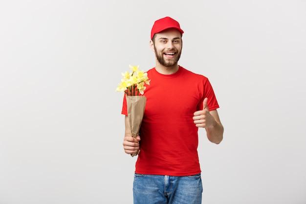 Portret van de gelukkige man die van de bloemlevering mooie boeketbloem houden en duim u tonen