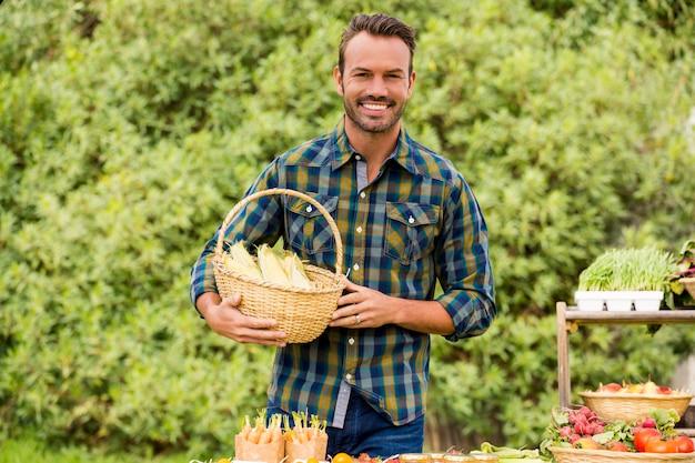 Portret van de gelukkige mens die organische groenten verkoopt
