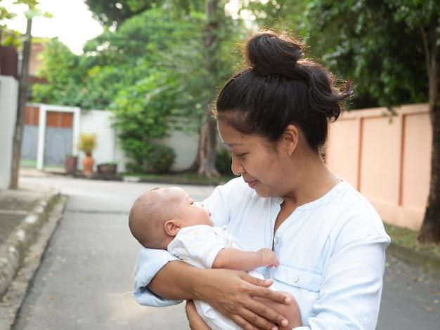 Portret van de gelukkige moeder die van azië zijn pasgeboren zoete geklede baby houden.