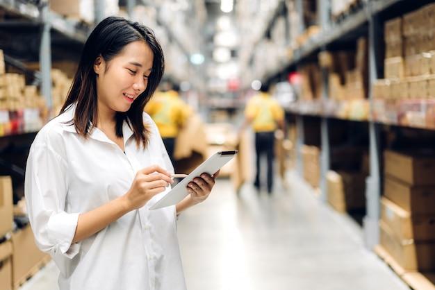Portret van de glimlachende aziatische vrouw die van de managerarbeider en details op tabletcomputer staan voor het controleren van goederen en leveringen op planken met goederenachtergrond in magazijn