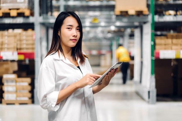 Portret van de glimlachende aziatische vrouw die van de managerarbeider en ordedetails op tabletcomputer bevinden