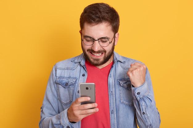Portret van de glimlachende gelukkige mens die denimjasje en rood overhemd draagt, vuist dichtklemt en slimme telefoon in handen houdt