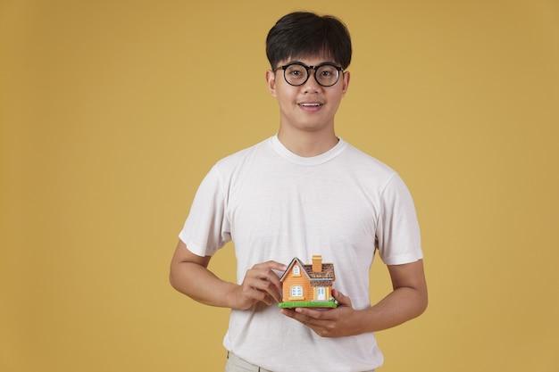 Portret van de glimlachende gelukkige vrolijke jonge aziatische mens kleedde zich terloops met geïsoleerd huishuismodel. aankoop van onroerend goed concept