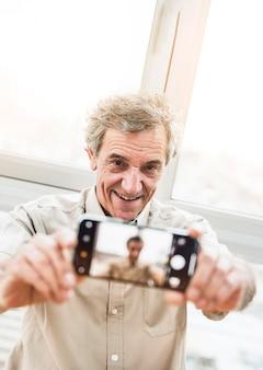 Portret van de glimlachende hogere mens die selfie met smartphone nemen