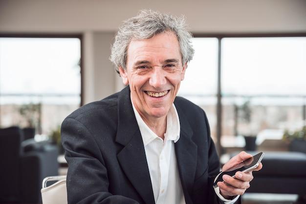Portret van de glimlachende hogere mens die slimme telefoon houdt