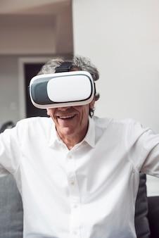 Portret van de glimlachende hogere mens die virtuele werkelijkheidsbeschermende brillen dragen