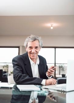 Portret van de glimlachende hogere mens met digitale tablet en laptop op glas weerspiegelend bureau