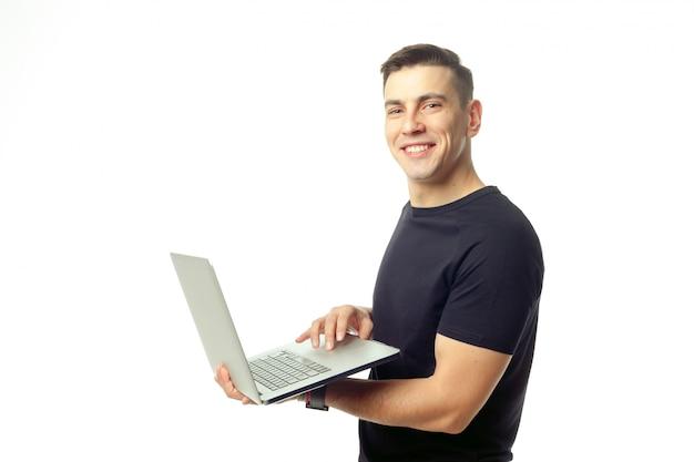 Portret van de glimlachende jonge geïsoleerde mens met laptop