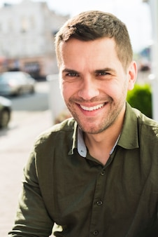 Portret van de glimlachende jonge mens die camera bekijkt