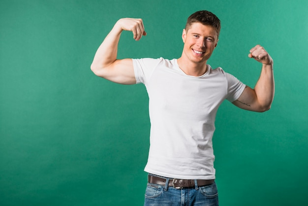 Portret van de glimlachende jonge mens die zijn spier buigt tegen groene achtergrond