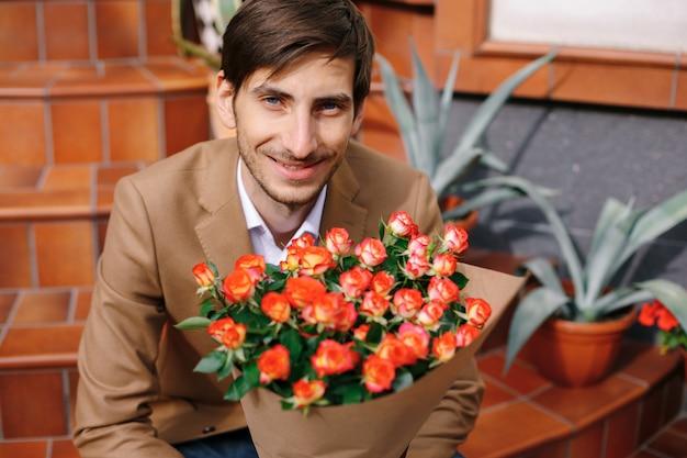 Portret van de glimlachende knappe mens die een boeket van bloemen houdt
