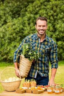 Portret van de glimlachende knappe mens die organische groenten verkopen