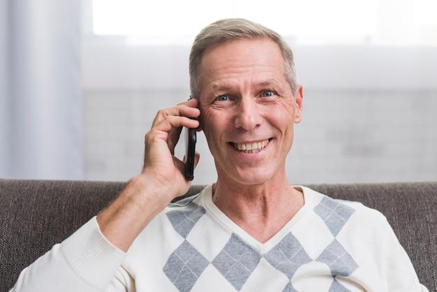 Portret van de glimlachende mens die bij telefoon spreekt