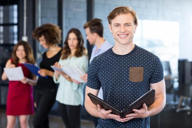 Portret van de glimlachende mens die een document houden terwijl collega's die zich erachter in bureau bevinden