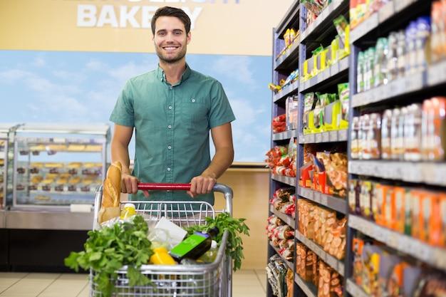Portret van de glimlachende mens die met zijn karretje op doorgang lopen