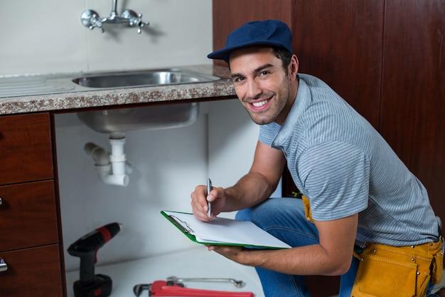Portret van de glimlachende mens die op klembord schrijft
